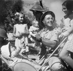 British soldiers play with babies in Solarino, Sicily - Italy 1943