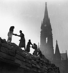 Women form a human chain to carry bricks used in the reconstruction of Dresden, March 1946, after allied bombing had destroyed the city in February 1945. The steeple of the wrecked Roman Catholic cathedral can be seen in the background.  Photo by Fred Ramage/Keystone Features/Hulton Archive/Getty Images