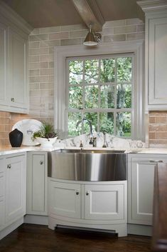 Design Galleria  ~Ivory kitchen cabinets with glass subway tiles backsplash, stainless steel curved front apron sink, marble countertops and Boston Functional Library Wall Light.