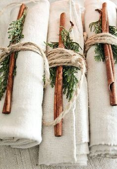 Rustic place settings- rough cloth napkins tied with twine, a cinnamon stick, and evergreen.  If you add a gift tag they could double as name cards too.