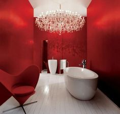Super modern, sleek design... Who can resist? The red is inviting. The chandelier is extraordinary. And the shiny white tub makes us feel clean just looking at it. Love it!