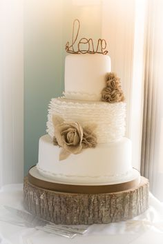 "Just lovely for an outdoor, country themed wedding day! (Although, I'm not so sure about the word ""LOVE"" on the top of the cake...I may have gone for more earth-toned flowers draping down the side, or a significant symbol to the couple in matching colors)."