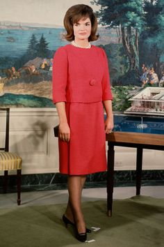 The First Lady Jacqueline Kennedy prepares for her televised tour of the restored White House ~ February 14, 1962. Although it was broadcast in black and white, she wore this vivid red dress.
