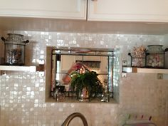 """Above my sink. I just put the small shelves in, from Ikea. When I originally redid the kitchen we indented this to form a """"window"""" since I didn't have one above the sink, added a mirror behind a leaded glass window."""