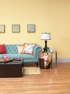 blue couch with warm yellow wall and pops of red