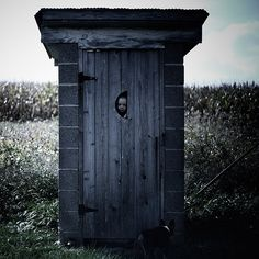 abandoned outhouse in an abandoned graveyard in an abandoned church in a cornfield..