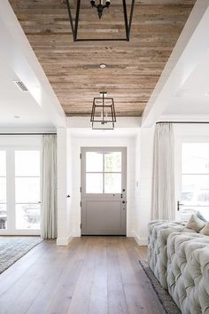 Modern Farmhouse Gray Glass Panel Door with Iron Lanterns Hanging from a Plank Ceiling Over a Gorgeous Wood Floor.
