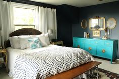 navy bedroom with gold accents, turquoise dresser