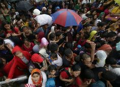 Typhoon survivors jostle to get a chance to board a C-130 military transport plane, Tuesday Nov. 12, 2013 in Tacloban city, Leyte province, central Philippines. Thousands of typhoon survivors swarmed the airport on Tuesday seeking a flight out, but only a few hundred made it, leaving behind a shattered, rain-lashed city short of food and water and littered with countless bodies. (AP Photo/Bullit Marquez)