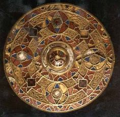 7th C. A circular red, blue and gold brooch.