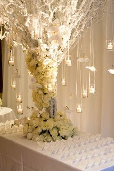 Recreate with backyard branches planted in tall cylinder of cement; spray painted with frosted white paint; gorgeous flowers glued up and around with hanging flowers or crystals.