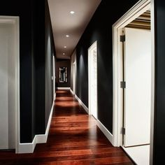 black walls  + white trim + rich wood+lighting--something about this is very attractive.