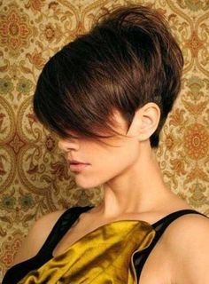 Short hair with wispy long bangs and cropped short in the back with lots of volume.