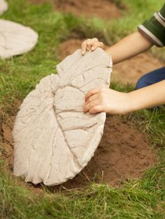 How to make a garden path:  Materials: large plant leaves, powdered cement mix, large plastic container, putty knife, cardboard & sand.