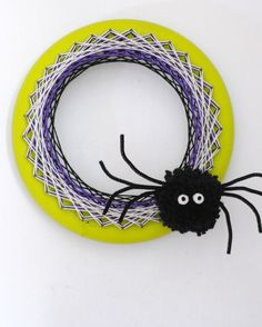 Kids can help loop the string around the pegs for a creepy yet creative #Halloween door decoration. Just add a pipe cleaner spider!
