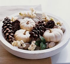simple centerpiece or coffee table decor with white pumpkins + pinecones in a shallow bowl or planter