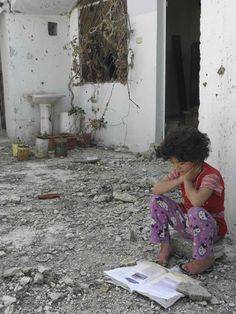 A Syrian girl reads a book in her damaged house in Talbisa area in Homs, northern Syria April 10, 2012.