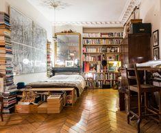 Bookshelves and stacks of books in an AMAZING Paris studio apartment.