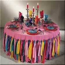 Tie fabricss to precut holes in a table cloth for a festive look.