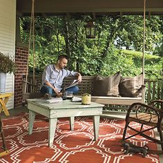 Bungalow Porch with rustic swing and table and bold graphic rug via Southern Living. #porch