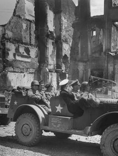 After invasion of Normandy, June, 1944, travelling past bombed out French buildings, is a jeep carrying U.S. Generals (backseat, L-R) Courtney Hodges, George Marshall and Dwight Eisenhower    http://www.3ad.com/history/courtney.hodges/photos.htm