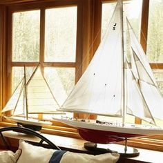 Two Sailboat Models in front of windows