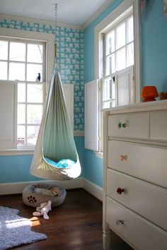 See the dog cozy in its bed, love the hanging seat better than an egg chair for a bedroom also love the odd draw knobs