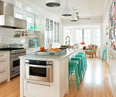 Modern kitchen island with seating, love the teal mixed with the white cabinetry and warm floors.