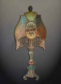 Beautiful carved candlestick style vintage lamp with custom shade. Shade style was originally designed for Stevie Nicks. Shades is hand dyed from misty green into coppery peach and covered with metallic laces and fabulous victorian metallic appliqués. Hand beaded glass fringe with Swarovski crystals.