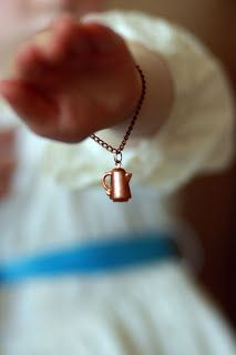 bright copper kettles (bracelet)...and a girl in a white dress with a blue satin sash!