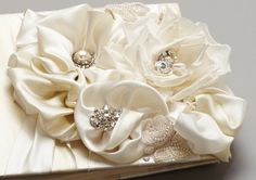 { Layers of satin silk come together in forms of beautifully ornate hand-made florals in this exquisite guestbook. Fresh water pearls, swarovski crystals, and beaded lace detail add an opulent and elegant look to any guestbook table. }