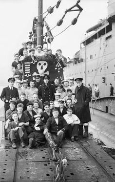 The crew of HM Submarine Thunderbolt display their 'Jolly Roger' on the Submarine Depot Ship HMS Forth in Holy Loch, Scotland, after a successful patrol in the Mediterranean, 27 March 1942.