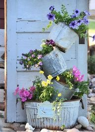 Love these old galvanized containers stacked as a flower planter! Really dented and junky. Perfect!