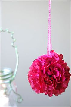 Easy way to make hanging flower balls. Wiffle balls from dollar store, dollar store fake flowers, pull the stems off the flower, hot glue around the circle in the wiffle ball, press flower into the hole making sure the bottom of the flower touches the glue, keep going until the ball is full of flowers, then hang with a ribbon. Must try!