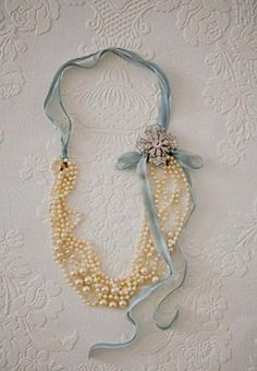 Fold beads in half, tie ribbon, add charms flower or a brooch to hide fold. -LARGE PHOTO