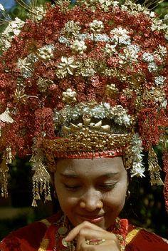 Indonesia | A bride wears an elaborate floral headdress at her wedding in Sumatra. | © Charles & Josette Lenars