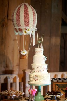 Whimsical wedding cake with mixed buttercream layers, ruffles & bunting.  Hot air balloon decor accent over dessert table |  Rustic Barn Wedding Skinner Barn Vermont  http://storyboardwedding.com/jessica-poole-wedding-anniversary-skinner-barn-vermont/