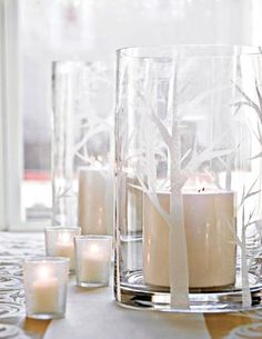 Give glass a temporary snowy tree look. Draw a design on adhesive shelf paper, cut it out with a crafts knife or scissors, and stick to hurricane. Peel off the top and spray exposed areas with faux snow from a crafts store. Let dry. If the tree design seems too intricate, go for simple geometric shapes: circles, rectangles, triangles, etc.