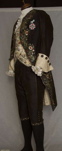GENT'S FOUR PIECE FORMAL COURT SUIT, c. 1820. Coat & breeches of dark brown cut/uncut velvet to blue satin ground; coat embroidered in polychrome silk large scale florals, gold metallic cord & crimped foil flowers, 20th C. Maltese cross paste insignia (WHY?) coat collar & original cuffs removed.