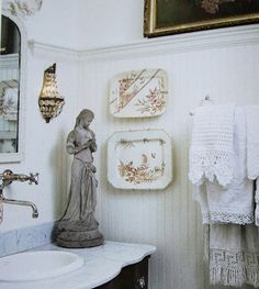 Faucet mounted on the wall, sconce, statue, towels, chair rail, dark antique art above, scalloped marble countertop vanity.