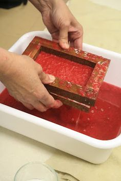 filling the mould and deckle with recycled paper pulp