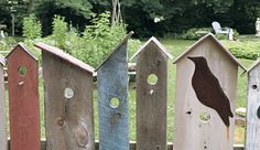 A whimsical plank fence in the shape of birdhouses