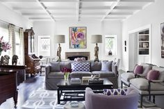 An eclectic mix of styles in this purple and gray living room with a gray sofa, purple armchair, ikat print pillows, an Asian style coffee table in black and a matching set of lamps on a sofa table
