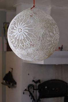 Cover doilies in wallpaper glue, glue them to balloon, pop balloon when dry and...viola. Could be a pretty wedding reception decoration.