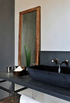 Loving this bathroom! The wood frame, the faded metal detailing and the fact that the black isn't a mirror-shine finish, makes this bathroom very sophisticated without coming across as pretentious.