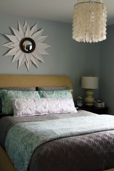 Upholstered mustard yellow bedframe. Gray duvet cover. White pintucked pillow. Starburst mirror.