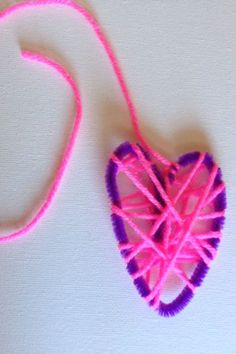 Yarn wrapped hearts are a great fine motor activity for little kids to make and then put on display for Valentine's Day.