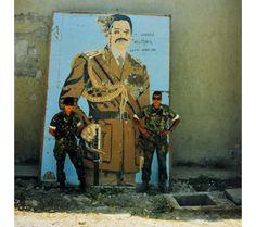Marco Kroon poseert met een collega bij een bewerkt portret van Saddam Hussein.