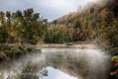 Mist rising on Vermont river with early autumn color in the trees above