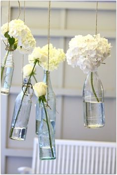 Flowers in hanging bottles.